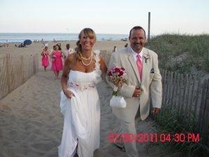 bride-groom-walking-up-beach-after-wedding